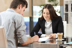 Client signing a document in an office. With a businesswoman looking the contract Stock Photos