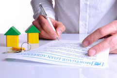 Client signing the mortgage loan agreement with small wooden hou Stock Photography
