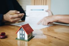 Client signing a real estate contract in real estate agency selective focus at house model royalty free stock photography