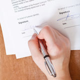 Client signs an agreement by silver pen Stock Photo