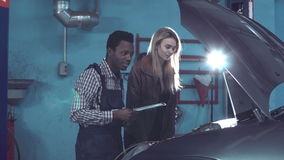 The client signs in form in car service. Young african mechanic check engine then woman owner of the car sign form of car repairing stock footage