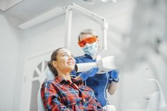 Client smiling while dentist in blue uniform holding x-ray. royalty free stock photo