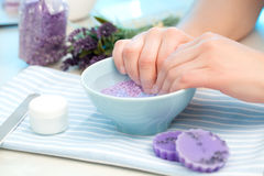 Manicure. Client soaks her hands in a bowl of fragrant water before manicure royalty free stock photography