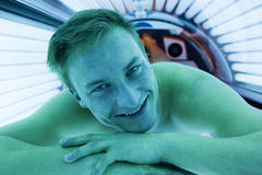 Client in a solarium on tanning bed Stock Photography