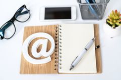Client support service. Contact us for feedback. Desktop with notepad, smartphone, glasses and email symbol. Top view royalty free stock photography