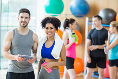 Client and trainer looking at tablet pc. At the gym Royalty Free Stock Images