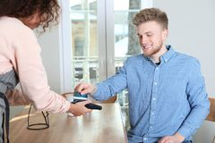 Client using credit card machine for non cash payment. In cafe royalty free stock photos