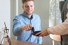 Client using credit card machine for non cash payment. In cafe stock images