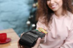 Client using credit card machine for non cash payment indoors. Closeup stock photography