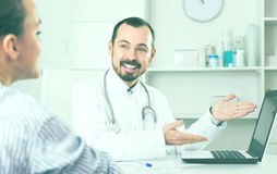 Client visiting consultation with man positive doctor Stock Photo