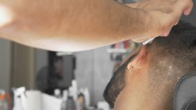 Client visiting luxury barbershop. Professional barber uses a straight razor shaving his client. Male customer visits a barbershop, elegant young man shaves his stock video