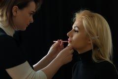 Clientagelesezeitschriften in einem Warteraum Bilden Sie Stilist malt Lippen mit einem Bleistift zum Kunden Stockbild