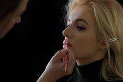 Clientagelesezeitschriften in einem Warteraum Bilden Sie Stilist malt Lippen mit einem Bleistift zum Kunden Stockfotos