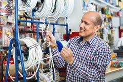 Cliente agradable masculino maduro que compra cable externo imagenes de archivo