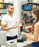 Cliente al negozio che paga allo scrittorio del registratore di cassa Immagini Stock Libere da Diritti