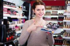 Cliente alegre de la mujer que decide sobre artículos del maquillaje en los cosméticos s Foto de archivo libre de regalías