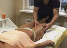 Cliente apto de la mujer de la morenita que recibe masaje del cuerpo en el club del balneario cerca Imagenes de archivo