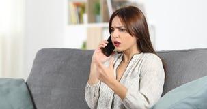 Cliente arrabbiato che chiama servizio di sostegno sul telefono video d archivio