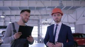 Cliente automatico di consigli degli impiegati di servizio in casco e punti a qualcosa alla stazione di riparazione archivi video