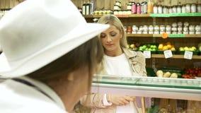 Cliente auxiliar de la porción de las ventas femeninas en charcutería almacen de metraje de vídeo