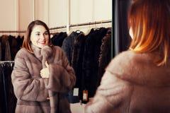 Cliente bonito de la muchacha que examina el nuevo abrigo de pieles foto de archivo