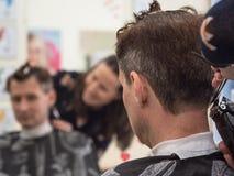 Cliente caucasico dell'uomo della disposizione del barbiere con la macchina del tagliatore in parrucchiere Processo maschio di tr immagine stock libera da diritti