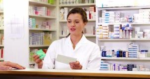 Cliente che dà le prescrizioni di medicina al farmacista stock footage