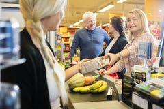Cliente che dà pacchetto al cassiere At Checkout Counter Fotografie Stock Libere da Diritti