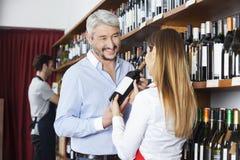 Cliente che esamina la bottiglia di Showing Red Wine della venditora Immagine Stock