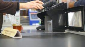Cliente che paga i prodotti al controllo Alimenti sul nastro trasportatore al supermercato Cassa con il cassiere ed il terminale archivi video
