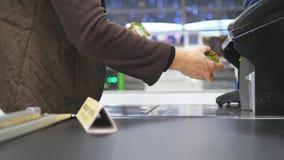 Cliente che paga i prodotti al controllo Alimenti sul nastro trasportatore al supermercato Cassa con il cassiere ed il terminale Immagine Stock Libera da Diritti