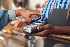 Cliente che paga il suo purchace del caffè con tecnologia del nfc Immagini Stock