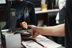 Cliente che paga tramite terminale moderno di pagamento facendo uso del telefono cellulare Pagamento di Nfc fotografie stock