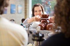 Cliente che prende caffè dal barista immagini stock