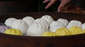 Cliente che sceglie e che compra i panini, bao o Baozi cotto a vapore di recente cucinato, gnocchi cinesi, alimento della carne d stock footage