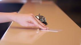 Cliente che suona la campana di servizio, receptionist che fornisce la chiave video d archivio