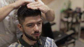 Cliente con la barba negra durante el pelo cortado en peluquería de caballeros Prepare, masculino almacen de metraje de vídeo