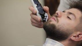 Cliente con la barba negra durante la barba que afeita en peluquería de caballeros Prepare, masculino almacen de video