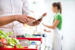 Cliente con la compressa al supermercato fotografie stock libere da diritti