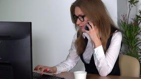 Cliente consultantesi del cliente della donna del mediatore del mercato finanziario sul telefono video d archivio