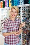 Cliente contente maduro da mulher que escolhe vários botões Fotografia de Stock Royalty Free
