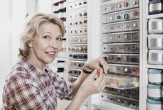 Cliente contente maduro da mulher que escolhe vários botões Foto de Stock Royalty Free