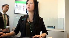 Cliente d'aiuto dell'impiegato asiatico attraente per depositare assegno video d archivio