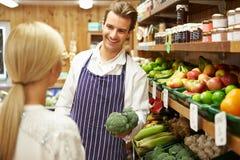 Cliente d'aiuto di aiuto al contatore di verdure del negozio dell'azienda agricola immagine stock libera da diritti