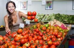 Cliente da jovem mulher que guarda tomates maduros frescos Fotografia de Stock Royalty Free