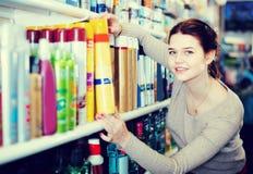 Cliente da mulher que decide em produtos dos cuidados capilares na loja foto de stock