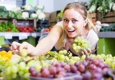 Cliente da mulher que escolhe uvas Imagens de Stock Royalty Free