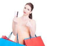 Cliente da mulher que mostra o cartão de crédito e que faz o polegar acima do gesto Foto de Stock