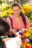 Cliente da mulher que toma a compra de florista do recibo Fotografia de Stock