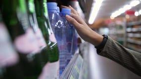 Cliente da mulher que toma a garrafa da água no supermercado Bebida da compra da menina do vegetariano 4K Slowmotion filme